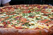 Pepperoni, pesto, broccoli, garlic, and tomato pizza